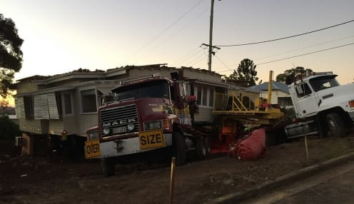 House cut in two and loaded on removal truck